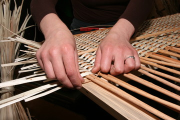 Female hands manually mastering wicker fabric