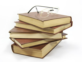 Stack of books with glasses isolated on white