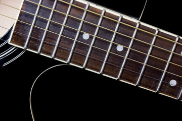 Close-up of fingerboard and strings on black acoustic guitar