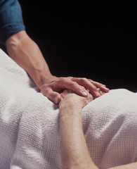 hand of a healer touches the hand of the elderly infirmed