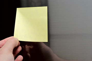 man removes blank post-it out of refrigerator door