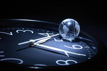 Litte glassy globe on dark background with watch