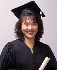 female asian college graduate with cap,gown and diploma