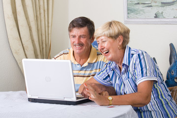happy senior couple using internet at home