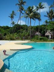 enfant au bord de la piscine qui se protège du soleil