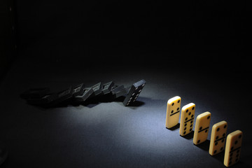 Black and white dominoes standing on dark background