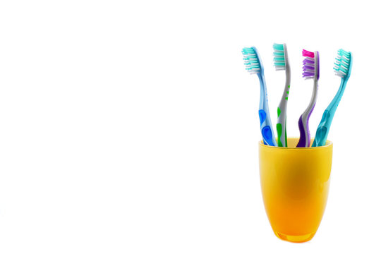 Four colorful toothbrushes in yellow mug isolated on white