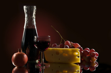 Still life with red wine, chese, grapes and garnet