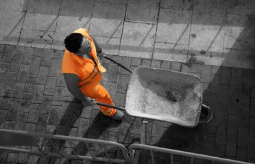 Spanish contruction worker, hand truck, orange security clothes