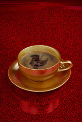 Gold cup of coffe on red background for your conceptual design