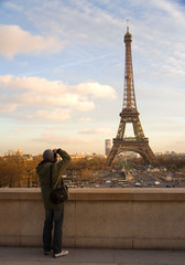 A tourist taking picture of the Eiffel Tower