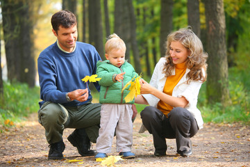 family with child in autumnal wood