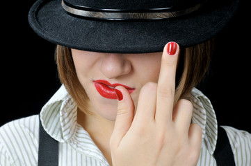 Reckless cool girl in black hat with middle finger up