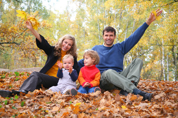 family of four sits in autumn park. parent hands up.