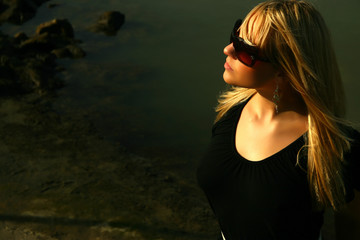 blond german girl at the black stones with sunglasses