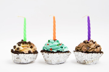 Three cupcake with icing and candles