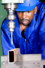 african industrial worker doing drilling work