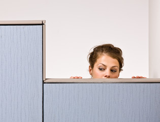 Businesswoman peering over cubicle wall