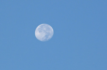 White moon, blue sky