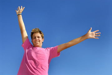 Boy arms wide open against a blue sky