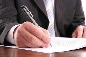 businessman writing on a official form using pen