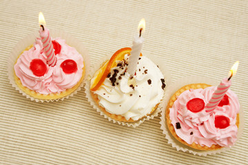 Three birthday cupcakes with candles.