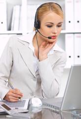 Blond business woman working in office, wearing headset
