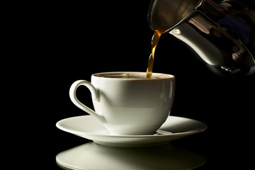 coffee pouring into white cup isolated over black background