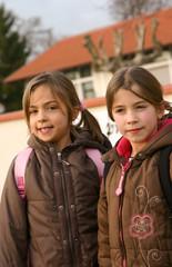 fillettes devant le mur de l'école
