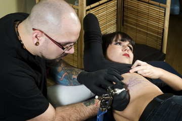 Tattooer tattooing client on rib cage