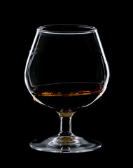 glass of cognac isolated over black background