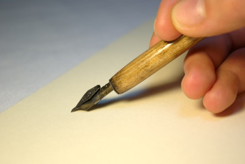 hand with ink pen writing letter
