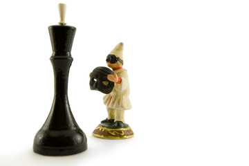 One chess figure and ceramic figurine of the clown on a white ba