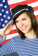 young sailor stands near the American flag and salutes