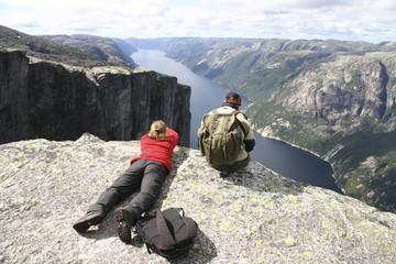 Wanderer bei Pause hoch über dem Lyse Fjord - Norwegen