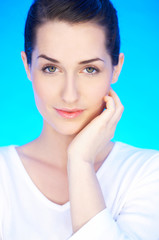 Portrait of 20-25 years old beautiful woman on blue background