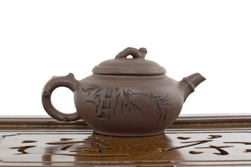 A teapot on a tea ceremony board on white background