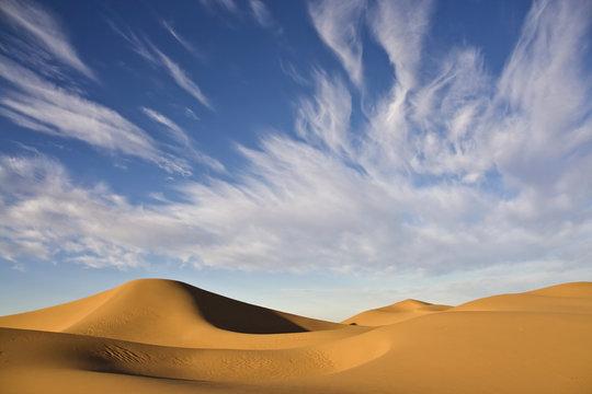desert dunes with cloudy blue sky