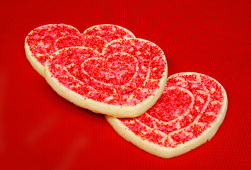 Three heart shaped valentine sugar cookies on red