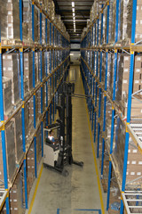 Warehouse worker manoeuvres pallet with reach truck
