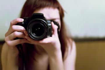 Jeune femme prenant une photo avec un reflex numérique en mains
