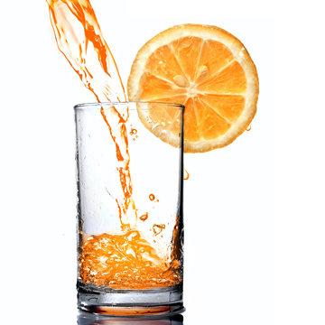 orange juice pouring into goblet with orange slice