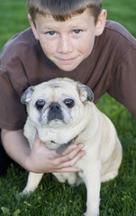 Young boy with his pet pug