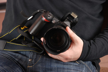Photographer holding photo camera (digital SLR) in hands