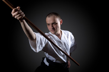 Man in white with wooden sword