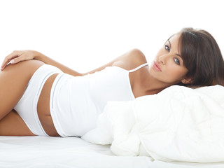 Portrait of beautiful woman in white bed