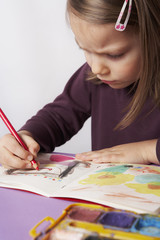 young girl concentrated on drawing a picture