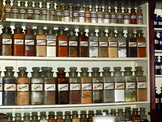 Rows of old jars with dry herbs, lined up on the shelves