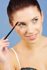 Portrait of pretty young woman applying mascara using lash brush