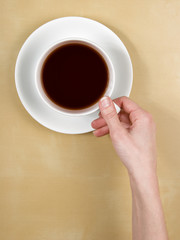 coffee - top view female hand holds a cup of tea on wood table -